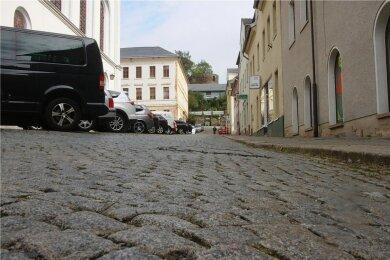 Der Kirchplatz in Elsterberg: Deutlich ist auf dem Foto der Höhenunterschied zwischen den parkenden Autos auf der linken Straßenseite und dem Gehweg rechts im Bild zu sehen. Dieser Zustand soll bei der Platzsanierung mit beseitigt werden.
