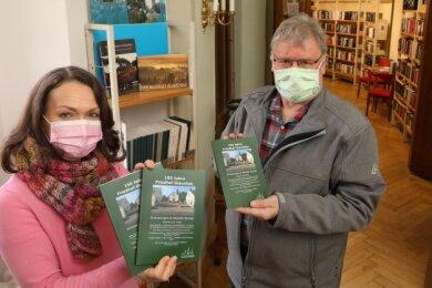 Peter Dittmann übergibt Exemplare der neuen Friedhofsbroschüre an die Leiterin der Bibliothek, Birgit Jakob.