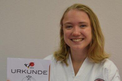 Stolz zeigt Luise Albrecht die Urkunde für bestandene Prüfung des braunen Gürtels. Als Belohnung erhielt sie ein besonderes Geschenk.