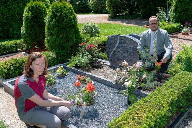 Bestatter Andreas Kohls und Ines Kästner, Mitarbeiterin für Grabpflege, an der Grabstätte auf dem Rochlitzer Friedhof, an der sich Diebe zu schaffen machten. Unter anderem ließen sie einen Ahornbaum mitgehen.