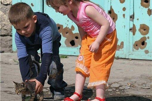 Kinder spielen vor einem Tor mit Einschusslöchern aus dem Kaukasus-Konflikt: Georgien sucht derzeit Frieden in einer West-Anbindung, von der auch viele Romane des Landes auf der Buchmesse erzählen.