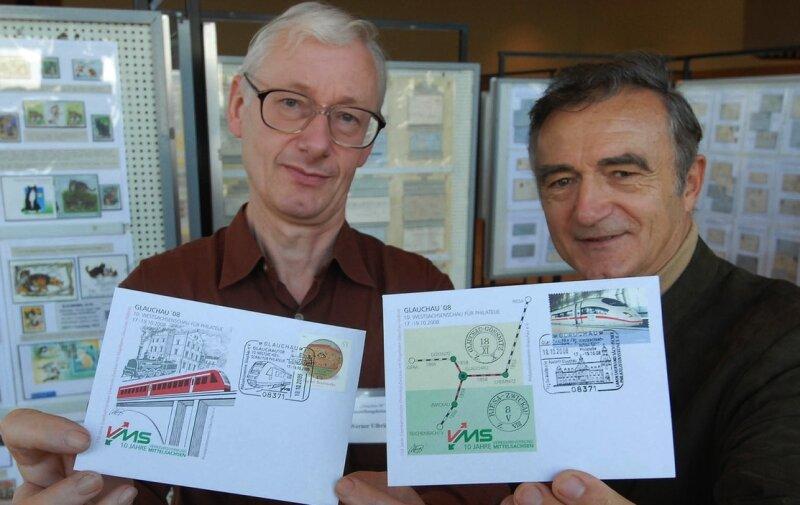 """<p class=""""artikelinhalt"""">Die zwei Sonderausgaben mit den beiden Sonderstempeln zur Briefmarken und Eisenbahnausstellung präsentieren Werner Ulbrich (links) und Harald Gehrt vom Glauchauer Philatelistenverein. </p>"""