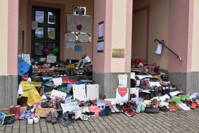 Etliche Schuhe vor dem Rathaus.