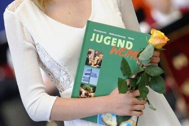 Eine Jugendliche mit einer gelben Rose und dem aktuellen Buch für die Jugendweihe-Teilnehmer.