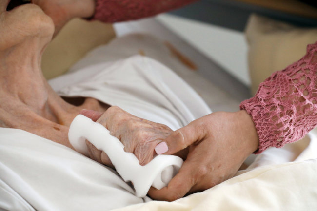 Eine Pflegeschwester hält die Hand einer alten Heimbewohnerin. Heimbewohner im Erzgebirge und ihre Angehörigen fürchten, sich das bald nicht mehr leisten zu können.
