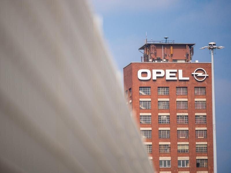 Der historische Opelturm steht hinter einem Zaun auf dem Werksgelände von Opel.
