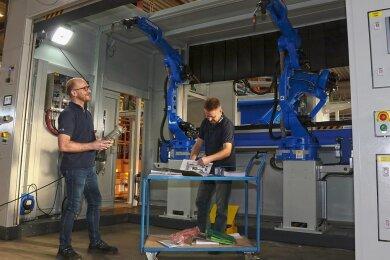 Die beiden Elektroingenieure Rico Ficker und Rico Meyer (r.) bereiten den Probebetrieb einer Roboteranlage vor, die in den nächsten Tagen ausgeliefert werden soll.