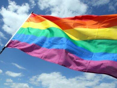 Eine Regenbogenfahne weht im Wind.