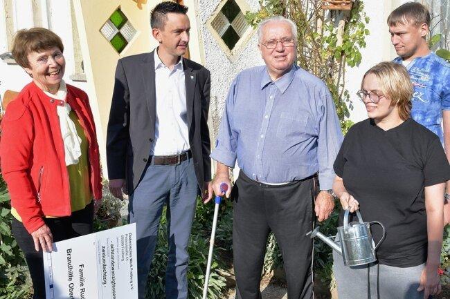 Irene Tempel, Vorstandschefin der Diakonie Freiberg, und Bürgermeister René Straßberger überreichten Spenden an Otmar, Julia und Robin Rudolph (v.l.), die bei einem Brand obdachlos geworden sind.