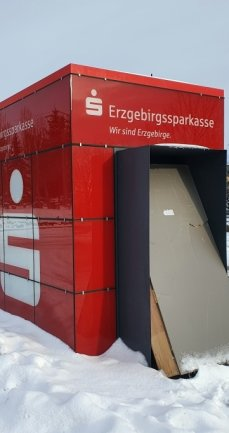 """Auf dem Parkplatz vor dem Einkaufsmarkt in Weißbach hat die Erzgebirgssparkasse einen """"Würfel"""" aufgebaut, der allerdings noch nicht in Betrieb ist."""