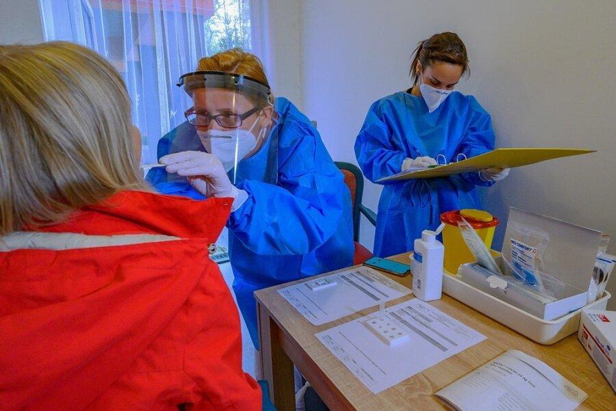 Schwester Nicole Oehme (Mitte) entnimmt in der Chemnitzer Seniorenresidenz Alexa eine Speichelprobe. Wohnbereichsleiterin Luisa Reh (rechts) protokolliert den Schnelltest.