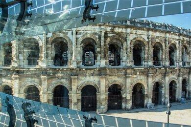 Wer durch die moderne Glaskachel-Fassade des 2018 eröffneten römischen Museums in Nîmes blickt, sieht in direkter Nachbarschaft das Wahrzeichen der Stadt. Die Arena zählt zu den besterhaltenen Amphitheatern der Welt - und wird noch immer genutzt.