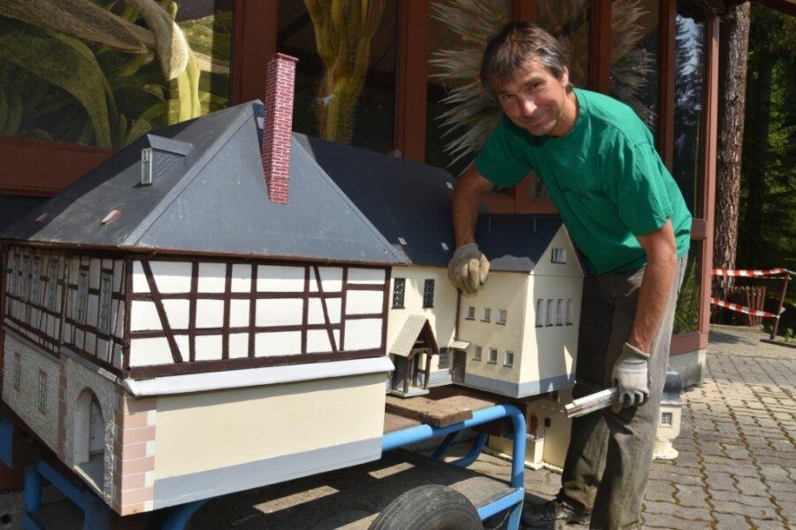 Rigo Schaller inspiziert das beschädigte Modell des Rodewischer Museums Göltzsch. Es wurde von der Flut mitgerissen und trieb über den Koi-Teich.