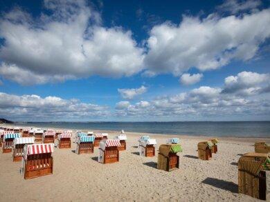 Geschlossene Strandkörbe stehen auf einem fast menschenleeren Strand an der Ostsee.