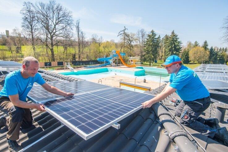 Mirko Kretzschmann (links) von der Firma Badbetreiber Erzgebirge und Knut Hartmann, Inhaber der Firma HFS Hartmann aus Ehrenfriedersdorf, montieren die Photovoltaikanlage auf dem Freibaddach.