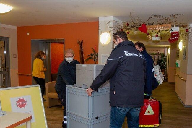 Anlieferung des Impfstoffs in der Senioreneinrichtung der Arbeiterwohlfahrt am Kastanienweg in Plauen: Das Team der Johanniter transportiert den Styropor-Karton mit den Ampullen in den extra eingerichteten Impfraum.