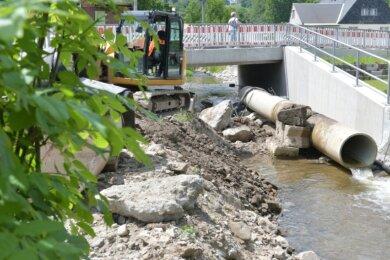 Mitarbeiter der Firma Hartmannbau aus Rechenberg-Bienenmühle sind bei den letzten Arbeiten am Neubau der Brücke über den Zethaubach in Mulda.