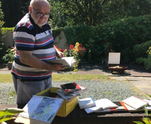 Zeitgeschichte im Postkarton: Rolf Ebert mit den 18 Notizbüchern, die Gäste der Quelle zwischen 1997 und 2014 vollgeschrieben haben.