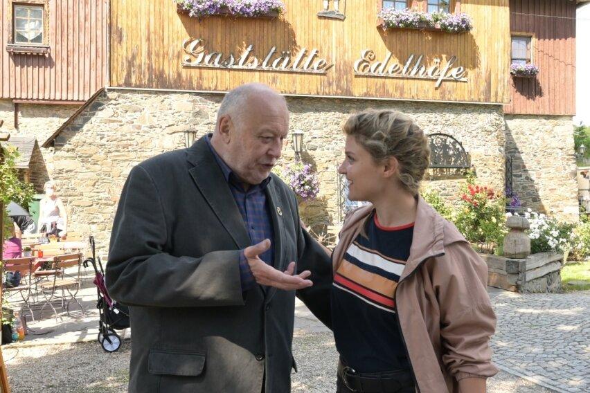 Schauspieler Thomas Thieme während der Drehpause im Gespräch mit Kollegin Lara Mandoki. Dahinter der veränderte Schriftzug der Gaststätte Edelhof in Alberoda.