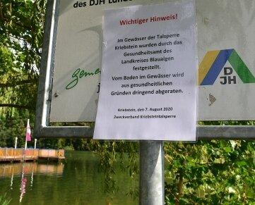 Am Ufer weisen mehrere Schilder auf Gefahr für Badende hin.