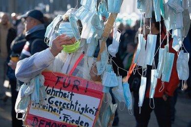 """Ausgestattet mit zahlreichen Nase-Mundschutz-Masken nahm eine Frau an der """"Querdenken""""-Demonstration in Leipzig am vergangenen Wochenende teil."""