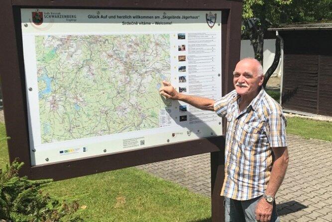 Wegewart Frank Köhler vom Erzgebirgszweigverein Schwarzenberg vor der Übersichtstafel zu Wanderwegen am Skigelände Jägerhaus.