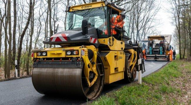 Zwischen Cossen und Berthelsdorf ist die Staatsstraße 242 wegen der Fahrbahnsanierung gesperrt. Am Freitag haben Mitarbeiter der Firma Chemnitzer Verkehrsbau auf einem Teilstück eine neue Schicht aufgebracht.