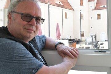 Thomas Erler schaut aus dem Filmprojektfenster zu, wie im Schlosshof Leinwand aufgebaut wird.