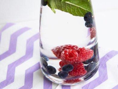 Bei Hitze ist mit Beeren und Minze versetztes Wasser besonders erfrischend:Aus Hygienegründen sollten Obst und Kräuter aber regelmäßig ausgewechselt werden.