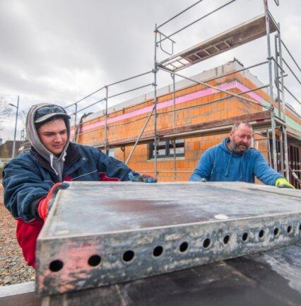 An der Stollberger Straße 31 in Neukirchen entsteht eine Eismanufaktur. Die Inbetriebnahme ist für diesen Sommer geplant. Lukas Müller und Thomas Eckhart vom Baugeschäft Sehm aus Tauscha bei Penig verladen Schal-tafeln für Beton.