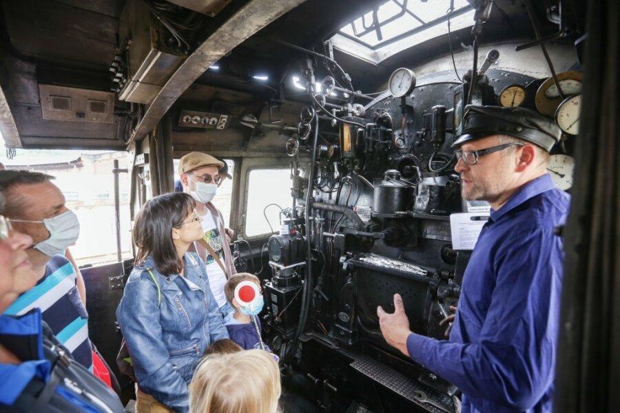 Lokführer Torsten Lämmel (rechts) erklärt den Besuchern, wie eine Dampflok funktioniert. Die Lok wurde 1943 gebaut und für den Gütertransport genutzt. Sie ist Teil der Ausstellung Schauplatz Eisenbahn, die am Samstag erstmals Gäste empfing. Die durften auch mitfahren.