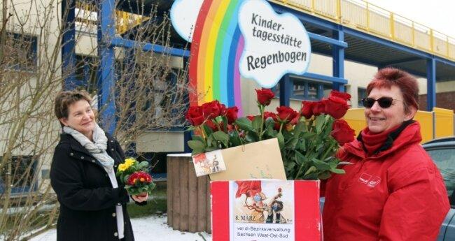"""Sybille Thiel von der Dienstleistungsgewerkschaft Verdi (r.) überbrachte Ulrike Richter, der Leiterin der Kita """"Regenbogen"""", 30 rote Rosen und zwei Primeltöpfchen für die Mitarbeiterinnen."""