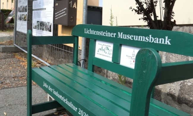 Die Museumsbank lädt zum Verweilen am wandernden Bauzaun ein.