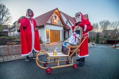 Seit 40 Jahren ist Matthias Groschwitz (rechts im Bild) im Ort als Weihnachtsmann unterwegs, für das kommende Fest hat er extra einen Schlitten zur kontaktfreien Geschenkübergabe umgebaut. Neben ihm ist sein Weihnachtsgehilfe Timm Reinhold.
