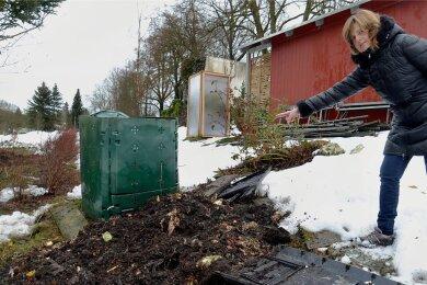Cornelia Stoll neben dem durchwühlten Kompost in ihrem Garten: Die Wildschweine hoben auf der Suche nach Nahrung selbst schwere Betonbohlen aus dem Boden.