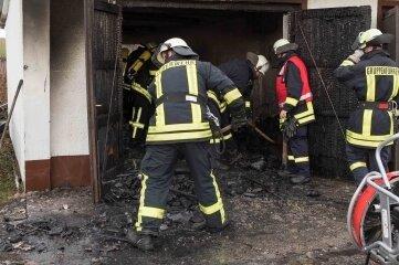 Mitglieder mehrerer Feuerwehren löschten das Feuer in der Garage.