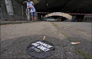 """""""Tanz' oder stirb"""" steht auf einem Aufkleber, der nach der tödlichen Massenpanik in Duisburg vor dem Tunnel zum Loveparade-Gelände auf dem Boden liegt. Nach der Massenpanik bei der Love-Parade in Duisburg mit 19 Toten wird die Veranstaltungsreihe nach Angaben von Organisator Rainer Schaller beendet."""