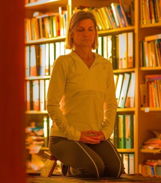 Blick nach unten und den Atembewegungen folgen: Ein Bänkchen unterstützt die aufrechte Haltung der Autorin im Fersensitz.