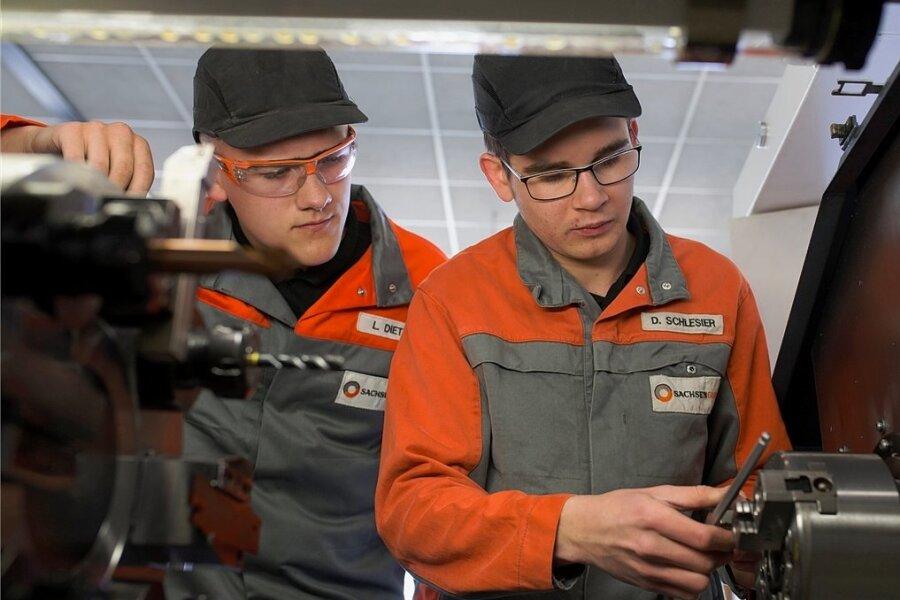 Leon Dietze (links) wird bei Sachsen Guss zum Gießereimechaniker ausgebildet, Daniel Schlesier zum Industriemechaniker. Hier sind sie mit dem Einstellen eines Hydraulikfutters einer CNC-Drehmaschine beschäftigt. Sachsen Guss sucht bei der Messe am Wochenende neue Auszubildende.