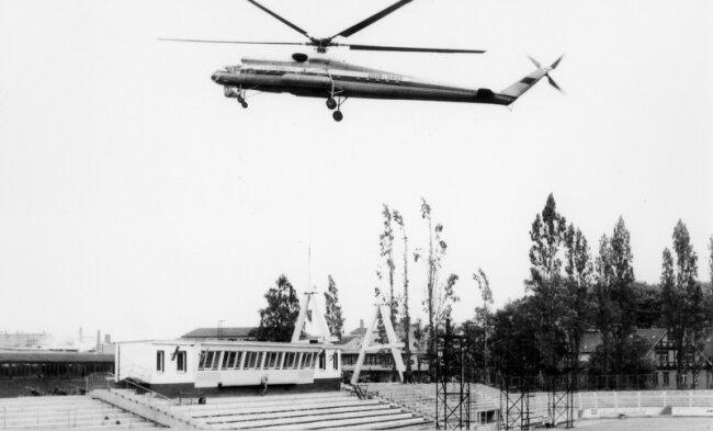 Ein Hubschrauber der Roten Armee liefert ein A-Profil für die Überdachung der Tribüne im Stadion an der Gellertstraße an.