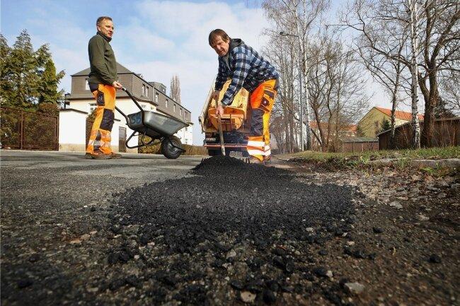 Tino Müller (links) und Gerd Wille vom Bauhof Lichtenstein beseitigen Schlaglöcher am Thomas-Müntzer-Weg. Nachdem der heiße Asphalt aufgetragen ist, kommen Gießkanne und Rüttelplatte.