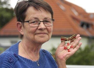 Monika Koch zeigt den Bundesverdienstorden, den sie für ihr Engagement erhielt.