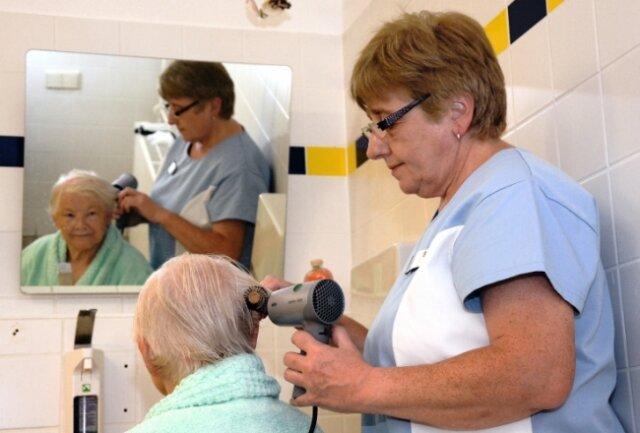 Nach dem Bad frisiert Birgit Kubitza die 82-jährige Hausbewohnerin Hannelore Haase.