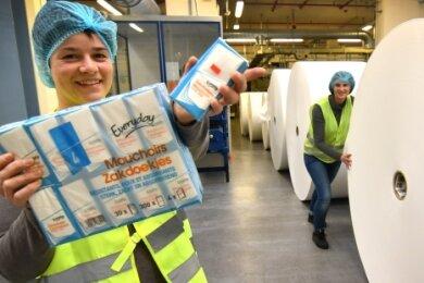 Aus solchen Rollen, wie sie Produktionsleiterin Franziska Krenkel (r.) zeigt, werden in der Wepa Papierfabrik in Kriebstein Taschen- beziehungsweise Kosmetiktücher hergestellt, wie sie Nicole Weber (vorn) in die Kamera hält.