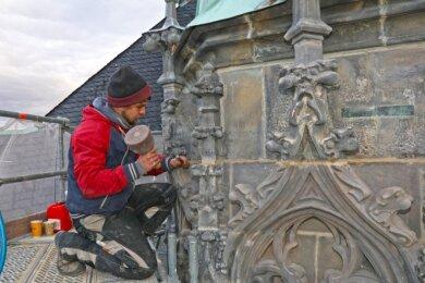 Philipp Lier bearbeitet als Bildhauer die neu eingesetzten Sandsteine unterhalb des Turmhelms so, dass sie sich denkmalgerecht in die Substanz einfügen.