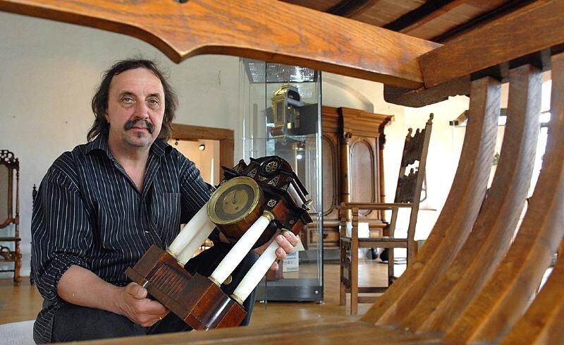 Thomas Heinicke bereitet auf Burg Kriebstein die neue Ausstellung mit historischen Uhren und Stühlen vor. Auf dem Bild zeigt er eine Wiener Tischuhr von 1830.