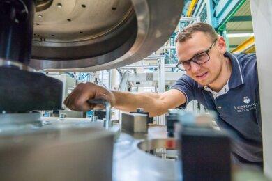 Industriemechaniker David Hellmich baut bei Blema Kircheis in Aue eine Werkzeugaufnahme für eine neue Kartonbodensiegelmaschine ein. Der 200-Mann-Betrieb ist Komplettanbieter von Verpackungsmaschinen, die auch in Krisenzeiten gefragt sind.
