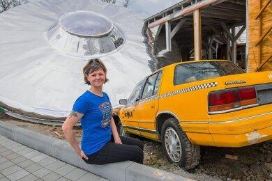 Ist hier ein Ufo auf ein Taxi gefallen? Nein, die Dekoration ist Teil des neuen Außenbereiches von Mr. Meyers Diner an der Zwickauer Straße. Mitarbeiterin Josie Haase wird am neuen Softeisstand arbeiten.