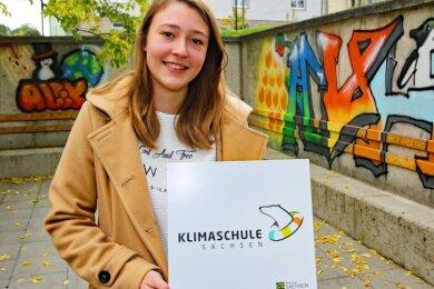 """Die 17-jährige Linda Rosenthal hat die Schule bei der Siegerehrung zur Klimaschule in Bautzen vertreten. An der Wand ist das neue Maskottchen des Gymnasiums zu sehen. Der Humboldt-Pinguin """"Alex"""" wurde von den zehnten Klassen im Kunstunterricht entworfen."""