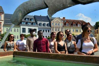 Auf dem Markt erfuhren die Studierenden aus Indien, Moldawien, Kamerun, Nigeria und dem Sudan Wissenswertes über das Rathaus, die Postsäule und die Marmeladentante genannte Brunnenfigur.